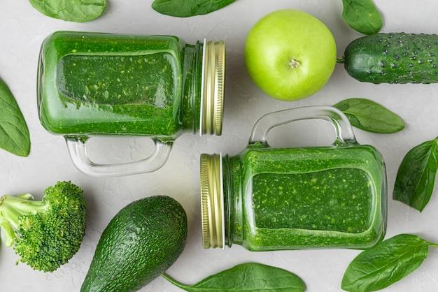 コンクリートの背景の上の瓶に新鮮な野菜や果物と緑の健康的なデトックススムージー。フラットレイ。上面図。健康的なデトックス朝食のコンセプト