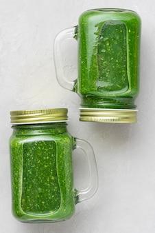 新鮮な野菜や果物を瓶に入れてコンクリートの背景に取り去る緑の健康的なデトックススムージー。フラットレイ。上面図。垂直方向