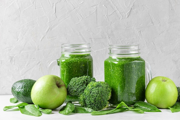Green healthy detox smoothie with fresh vegetables and fruits in jars on white wall. healthy detox breakfast concept. close up