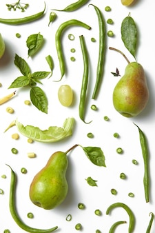 Green healthy drink. vegetable juice,pears, leaves of basil and beans on the white table. vegetarian food. detox