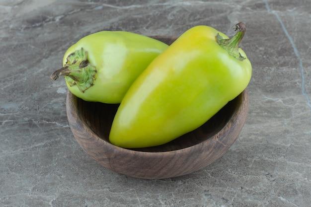Cibo sano verde. peperoni dolci organici in ciotola di legno.