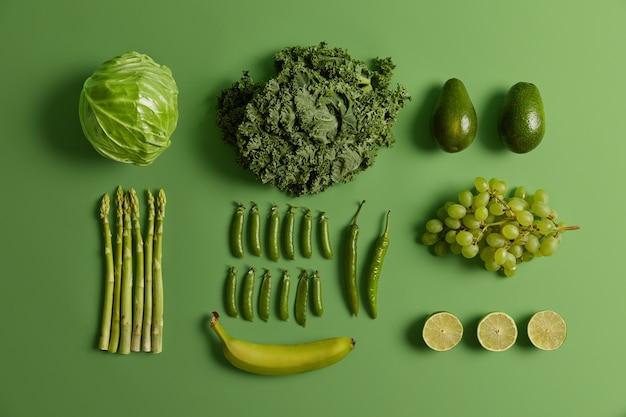 Зеленые здоровые сырые фрукты и овощи. свежая собранная капуста, лайм, авокадо, спаржа, горох, виноград, перец чили и банан, изолированные на ярком фоне. набор органических натуральных продуктов.