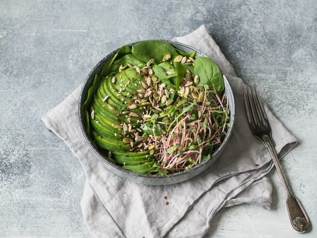 Green healthy salad of spinach, sprouts, avocados and various seeds