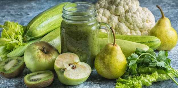 Зеленый здоровый коктейль из зеленых овощей и фруктов на сером бетонном столе. концепция здорового питания и диеты.