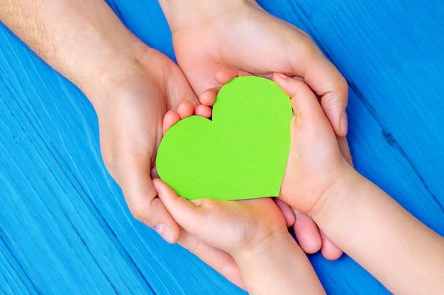성인과 어린이의 손에 녹색 마음.