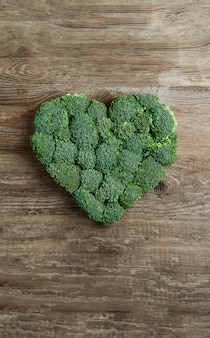 Green heart lined with broccoli on a wooden