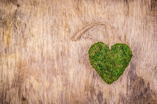 Green heart on wooden background