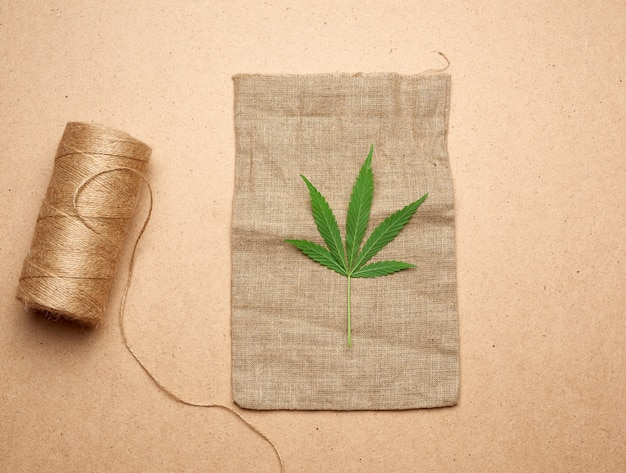 Green hemp leaf, skein with brown rope and empty bag on a brown wooden background