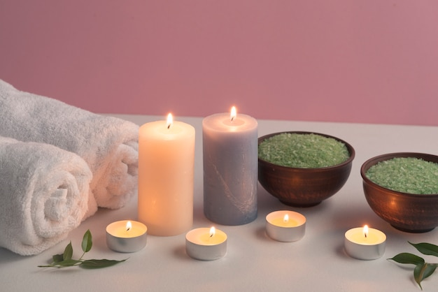 Green herbal bath salt and towels with illuminated candles on white table