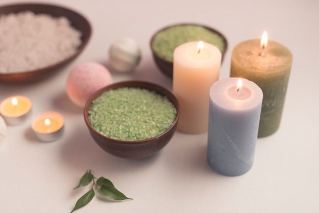 Green herbal bath salt with illuminated candles on white background
