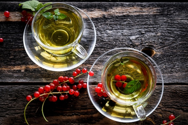 Green herbal tea with a berries in glass cup on wooden table
