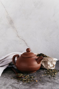 Green herbal teapot with dried tea leaves with napkin against wall