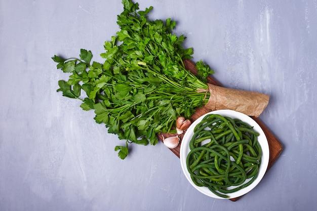 Зеленые травы и салат на синем