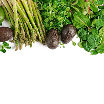 Зеленые травы, спаржа и черный авокадо на белом фоне. вид сверху.
