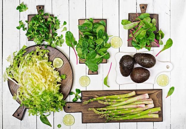 Зеленые травы, спаржа и черный авокадо на белом деревянном фоне. вид сверху.