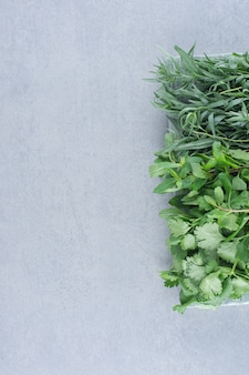 Assortimento di erbe verdi su sfondo grigio pietra.
