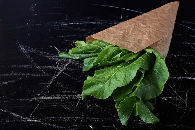 Green herbs in a paper wrap.