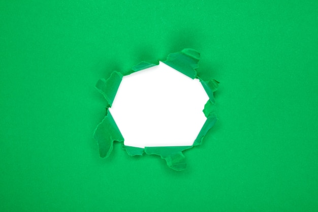Зеленая дыра в бумаге с порванными сторонами
