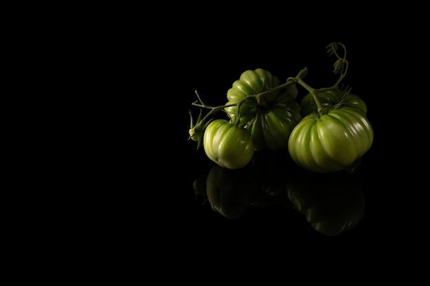黒の背景に緑の自家製の美しいトマト