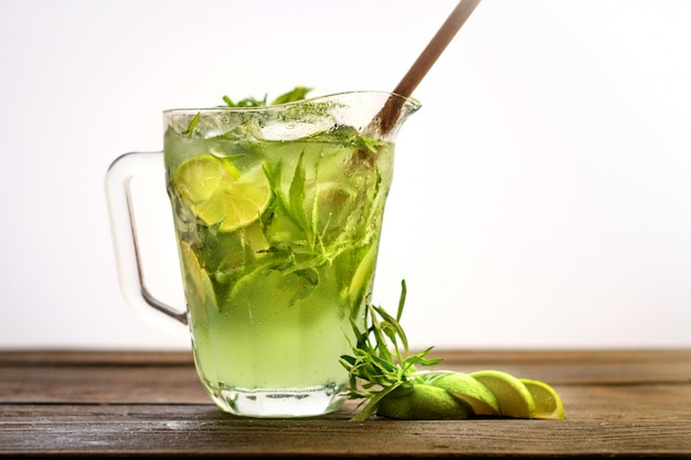 Green homemade lemonade with tarragon, lime and ice in a jar on wooden background