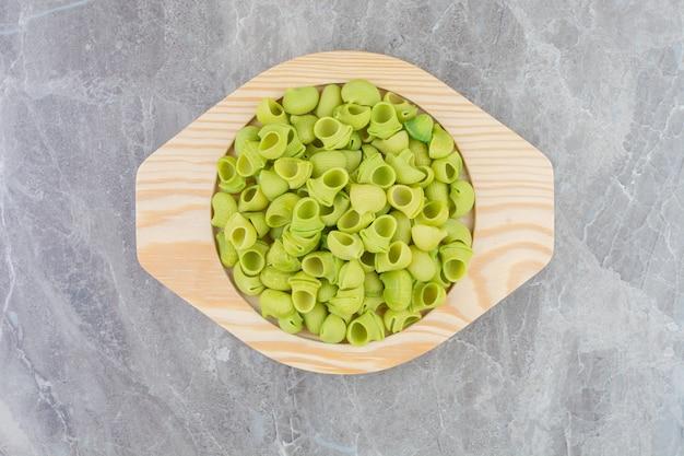 丸い木製の大皿に緑の自家製パスタ