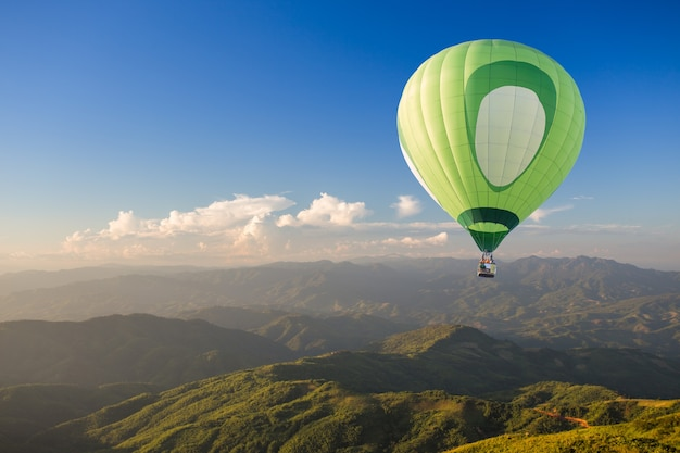 Green hot air balloon over the mountain at sunset
