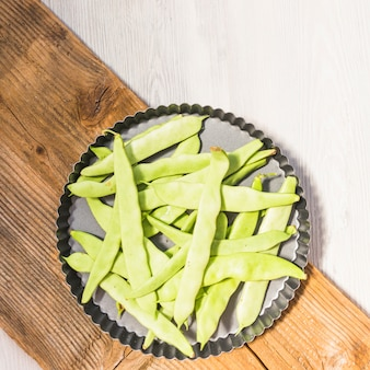 Green hyacinth beans on baking tray over wooden chopping board
