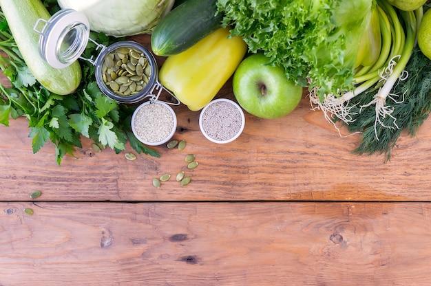 Зеленые гипоаллергенные овощи в деревянном ящике и семена. вегетарианская еда. селективный фокус, вид сверху.