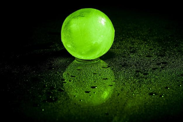 黒の背景に緑の氷球の反射。