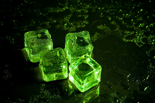 Green ice cubes reflection on black table background.