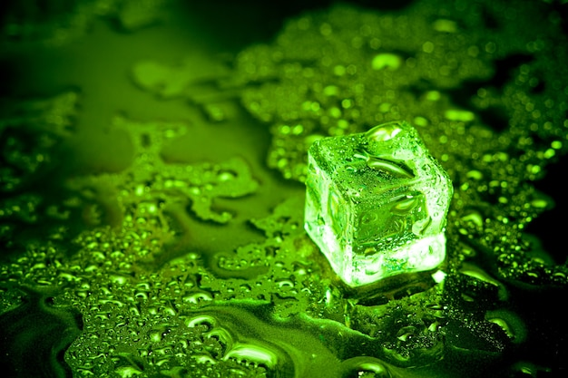 Green ice cubes reflection on black table.