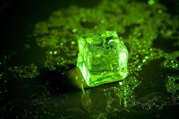 黒いテーブルの背景に緑の角氷の反射。