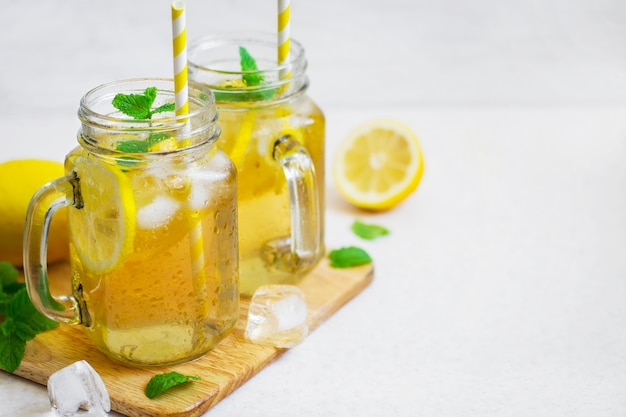 Зеленый ледяной чай с лимоном и мятой в стеклянной банке.
