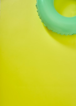 Green inflatable ring on yellow background
