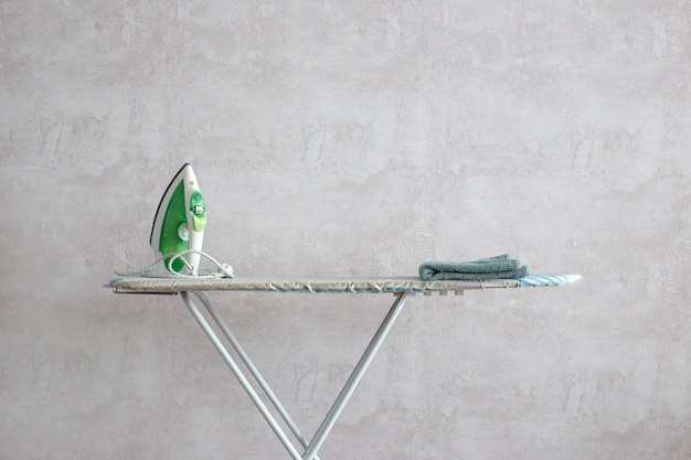 A green iron stands on an ironing board.