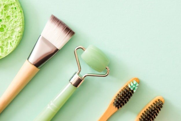 Green jade face roller, makeup brush, natural bamboo toothbrushes and sponges. flat lay style. modern self care beauty concept.