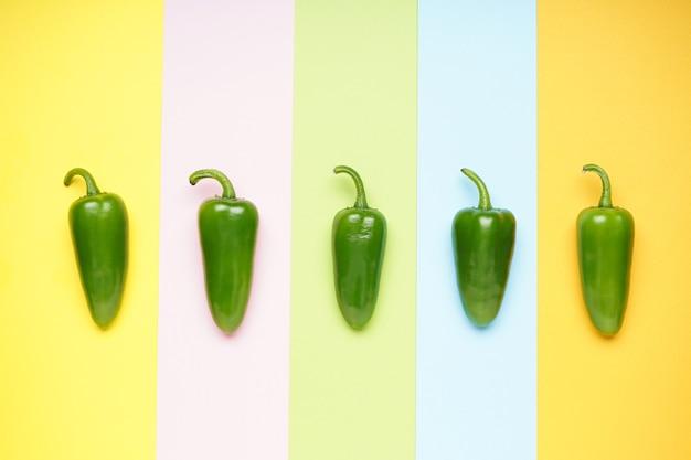 Зеленый перец халапеньо на красочном фоне. плоская планировка.