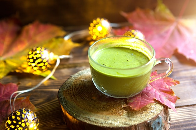 Green japanese matcha tea with foam in transparent cup on wooden table in autumn still life. warm atmosphere and comfort, lights garlands, red maple leaves, cinnamon sticks, pumpkin, cookies, slice.