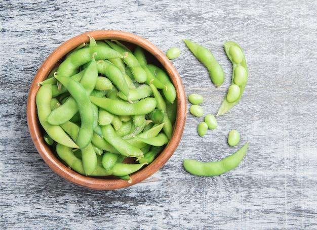 テーブルウッドの木のボウルの緑の日本の大豆