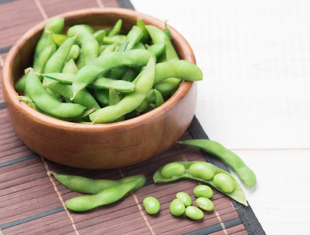 Green japanese soybean in wooden bowl on table wood