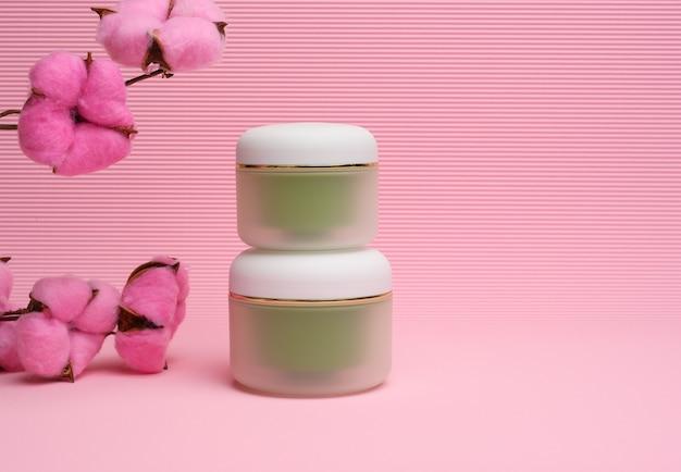 분홍색 배경에 화장품을 위한 녹색 항아리입니다. 크림, 젤, 혈청, 광고 및 제품 판촉용 포장, 모형