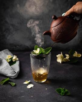 Зеленый чай с жасмином с мелиссой на керамических чайниках, найденных на черном камне