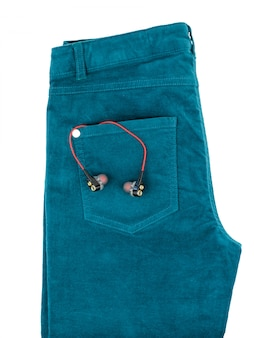 Green jeans with headphones in pocket isolated on white.