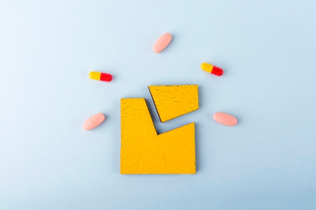 Green jigsaw puzzle pieces with different pills and medicines. concept of neurological disease treatment : autism, alzheimer's, dimension. copy space for text. awareness day supportive and acceptance