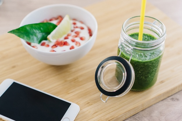 Green juice next to bowl of cereals with yogurt