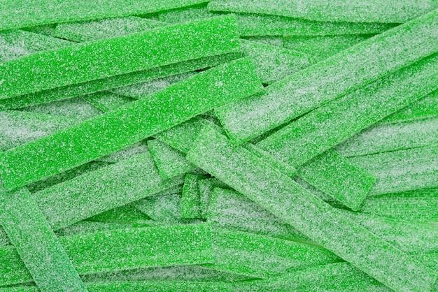 Green juicy gummy candies background. top view.