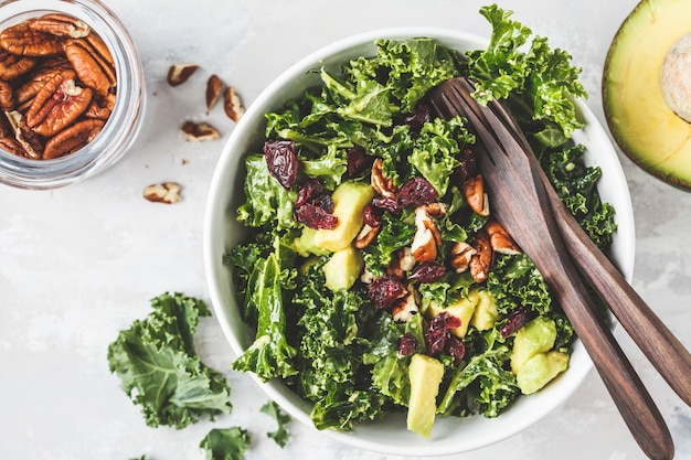 Green kale salad with cranberries and avocado in white bowl, top view. healthy vegan food concept.