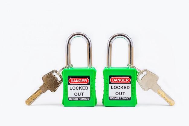 Зеленый ключ блокировки и метки для процесса, отключенного электричества, номер метки переключателя для электрического выхода бирки на белом фоне