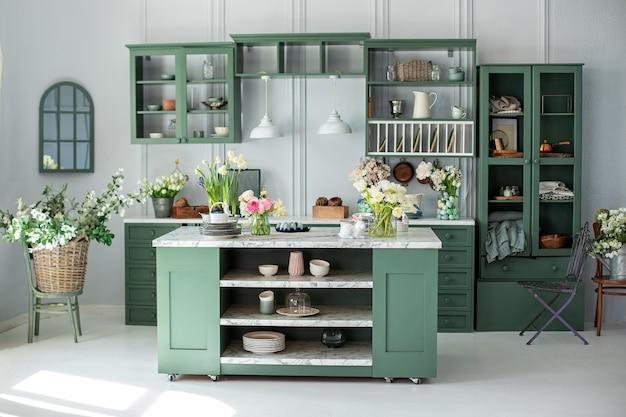 Зеленая кухня в деревенском интерьере с цветами и белым элегантным стенным фоном