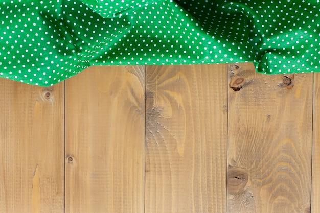 Зеленое кухонное полотенце на деревянной столешнице, предметы кухни, текстиль.